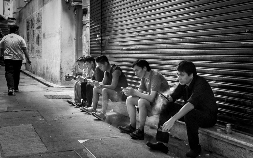 Men relaxing and taking a smoke break in a Mong Kok alleyway